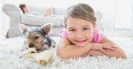 Mädchen und Hund auf sauberem Teppich